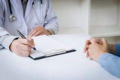 Ciérrese para arriba de paciente y de doctor de la medicina en un hospital/una clínica fotos de archivo