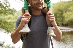 Ciérrese para arriba de padre que Carrying Son On lleva a hombros en paseo por el río foto de archivo libre de regalías