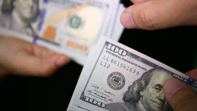 Ciérrese para arriba de pagar efectivo de las manos del hombre que cuentan hacia fuera cientos billetes de dólar en la mano de un almacen de video