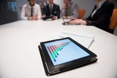 Ciérrese para arriba de panel táctil con los documentos del analytics en el meetin del negocio Fotos de archivo