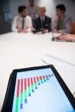 Ciérrese para arriba de panel táctil con los documentos del analytics en el meetin del negocio Imagenes de archivo