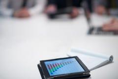 Ciérrese para arriba de panel táctil con los documentos del analytics en el meetin del negocio Fotografía de archivo libre de regalías