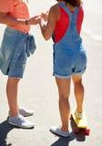Ciérrese para arriba de pares adolescentes con el monopatín al aire libre Fotografía de archivo
