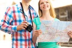 Ciérrese para arriba de pares con el mapa y de cámara en ciudad Imagenes de archivo