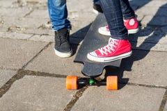 Ciérrese para arriba de pares con longboard en la calle Fotografía de archivo libre de regalías