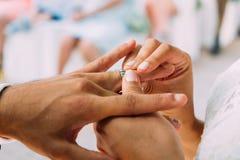 Ciérrese para arriba de pares de joven se casa nuevamente con las manos de la mujer que ponen el anillo de bodas del oro en finge imagenes de archivo