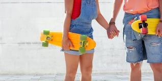 Ciérrese para arriba de pares jovenes con los monopatines al aire libre Foto de archivo libre de regalías