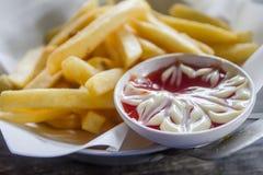 Ciérrese para arriba de patatas fritas y de salsa de tomate en la tabla Fotos de archivo