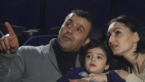 Ciérrese para arriba de películas de observación de una familia cariñosa feliz en el cine almacen de video