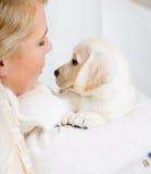 Ciérrese para arriba de perrito del abarcamiento Labrador de la mujer Imagenes de archivo