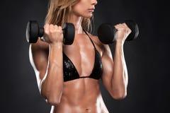 Ciérrese para arriba de pesas de gimnasia de elevación de la mujer muscular del ajuste. Foto de archivo