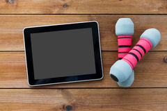 Ciérrese para arriba de pesas de gimnasia y haga tabletas la PC en la madera Imágenes de archivo libres de regalías