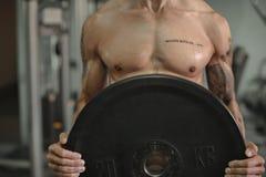 Ciérrese para arriba de pesos de elevación del hombre muscular joven en el fondo del gimnasio Foto de archivo libre de regalías
