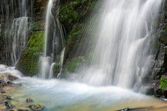 Ciérrese para arriba de pie de la cascada con la roca cubierta de musgo Fotos de archivo