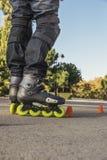 Ciérrese para arriba de piernas en el rollerskate que patina en el camino de la parte posterior Foto de archivo