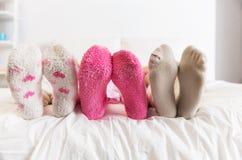 Ciérrese para arriba de pies de las mujeres en calcetines en cama en casa Foto de archivo libre de regalías