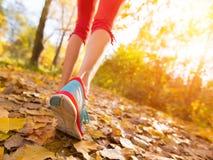 Ciérrese para arriba de pies de un corredor que corre en hojas Fotografía de archivo