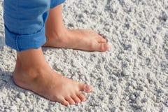 Ciérrese para arriba de pies del niño en una playa arenosa tropical Foto de archivo