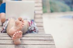 Ciérrese para arriba de pies del ` s del freelancer en la playa Imagenes de archivo