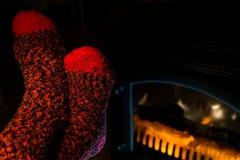 Ciérrese para arriba de pies en los calcetines lanosos que se calientan por la chimenea Imagenes de archivo