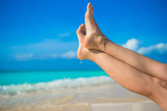 Ciérrese para arriba de pies femeninos en la playa arenosa blanca Imagenes de archivo