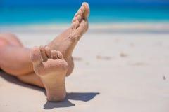 Ciérrese para arriba de pies femeninos en la playa arenosa blanca Imagen de archivo libre de regalías