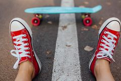 Ciérrese para arriba de pies y de tablero azul del patín del penique con las ruedas rosadas Fotos de archivo libres de regalías