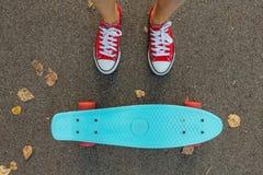 Ciérrese para arriba de pies y de tablero azul del patín del penique con las ruedas rosadas Imagen de archivo