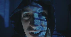 Ciérrese para arriba de programador loco del pirata informático en capilla con la reflexión del código binario en su cara en siti metrajes