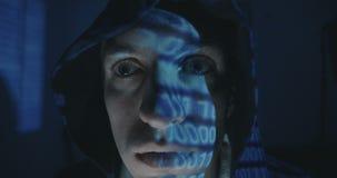 Ciérrese para arriba de programador loco del pirata informático en capilla con la reflexión del código binario en su cara en siti almacen de video