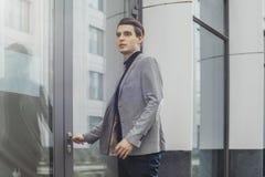 Ciérrese para arriba de puerta de abertura joven del hombre de negocios del centro de negocios moderno imagenes de archivo