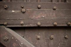 Ciérrese para arriba de puerta de madera pesada de un templo en Asia tachonó con b Fotos de archivo libres de regalías