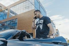 Ciérrese para arriba de salir atractivo del hombre del coche y de hablar por el teléfono móvil foto de archivo libre de regalías