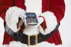 Ciérrese para arriba de Santa Claus Holding Credit Card Reader imágenes de archivo libres de regalías