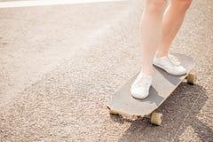 Ciérrese para arriba de señora que la pierna que descansa después de extremo monta su monopatín de madera del longboard Foto de archivo