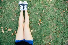 Ciérrese para arriba de sentarse asiático joven de la mujer solo en la hierba verde en el parque público Imagenes de archivo