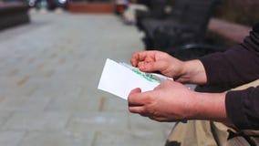 Ciérrese para arriba de sobre del efectivo adentro en manos Prima del dinero en un sobre de papel Un hombre que sostiene un sobre almacen de metraje de vídeo