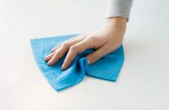 Ciérrese para arriba de superficie de la tabla de la limpieza de la mano con el paño Fotografía de archivo