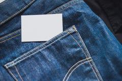 Ciérrese para arriba de tarjeta de visita blanca en blanco en bolsillo de los vaqueros Espacio vacío foto de archivo