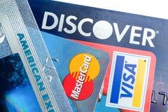 Ciérrese para arriba de tarjetas de crédito con descubren, American Express, visa y los logotipos de Mastercard en el fondo blanc Imagen de archivo libre de regalías