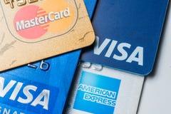 Ciérrese para arriba de tarjetas de crédito con los logotipos de Mastercard, de la visa y de American Express en el fondo blanco, Fotos de archivo