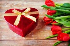 Ciérrese para arriba de tulipanes y de la caja rojos del chocolate Imágenes de archivo libres de regalías
