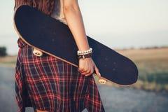 Ciérrese para arriba de un adolescente que sostiene el monopatín Foto de archivo
