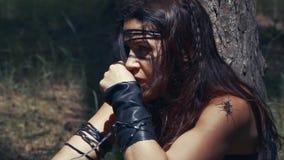 Ciérrese para arriba de un Amazonas joven en la piel y la ropa de cuero que se sientan debajo del árbol metrajes