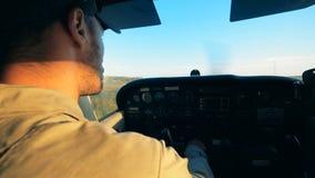 Ciérrese para arriba de un aviador de sexo masculino que pilota un avión mientras que se sienta en una carlinga almacen de video