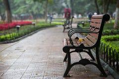 Ciérrese para arriba de un banco en el parque después de la lluvia Imagenes de archivo