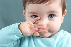 Ciérrese para arriba de un bebé que mira la cámara con los ojos azules grandes Imagen de archivo