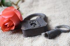Ciérrese para arriba de un candado viejo con una llave y un rosado subió fotografía de archivo