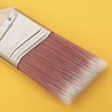 Ciérrese para arriba de un cepillo de pintura en un fondo vibrante Foto de archivo libre de regalías