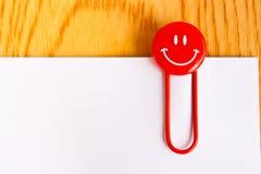 Ciérrese para arriba de un clip de papel rojo y de un Libro Blanco Imagenes de archivo
